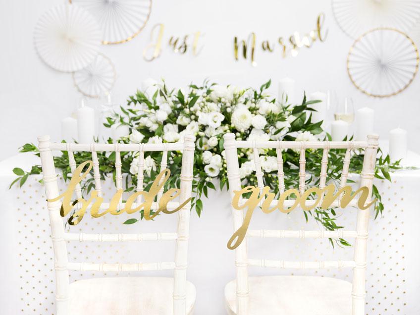 Veredel die Stühle des Brautpaars mit goldenen Stuhlschildern