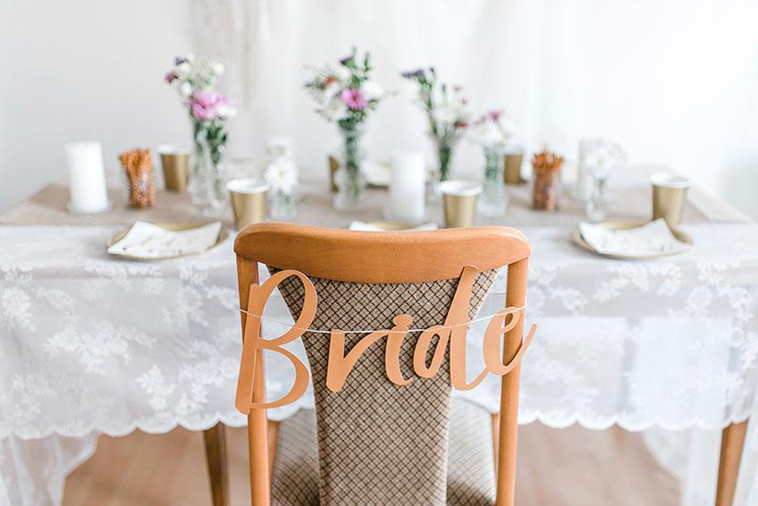 """Das selbstgemachte Girlanden-Stuhlschild """"Bride"""" macht den Platz der Bride-to-be zu etwas Besonderem (c) Carina Plößl Fotografie"""