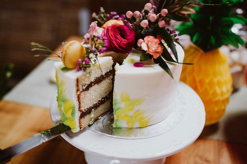 Tropisch verzierter Kuchen mit Pflanzen und Macarons
