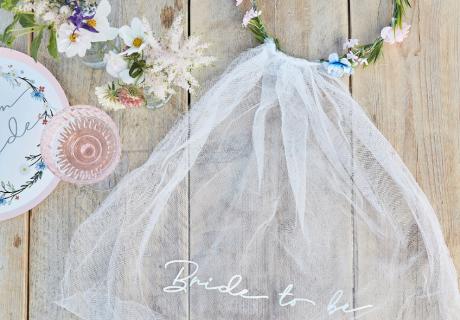"""Die Bald-Braut bekommt zum JGA Thema """"Boho-Brautparty-Picknick"""" einen Blumenkranz mit Schleier"""