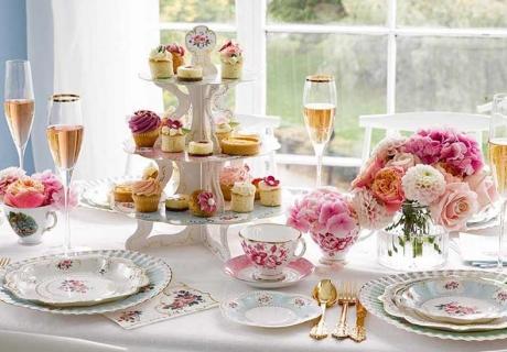 Der Kaffeetisch zur Landhochzeit wir mit Porzellangeschirr und filigranen Blütenmustern gedeckt