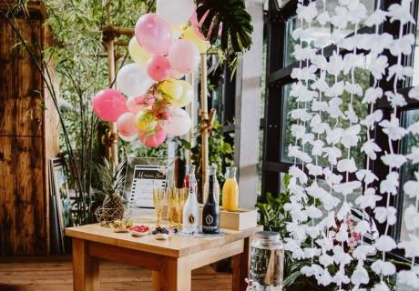 Dekoriere deine Mimosa Bar mit Ballongirlande und Blumenvorhang